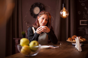 Close up portrait of adult businesswoman smiling while holding a cup of coffee. Relaxing in vintage coffee shop