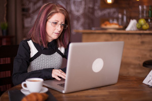 Close up portrait of adult businesswoman working on laptop and enjoying a morning coffee