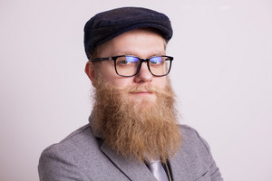 Close up portrait of bearded businessman with glasses over yellow background. Stylish beard. Handsome man.
