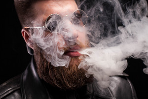 Close up portrait of bearded young man with sunglasses exhaling cigarette smoke over background. Stylish beard. Cool sunglasses.