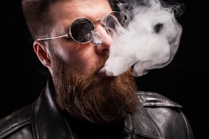 Close up portrait of confident bearded man wearing black leather jacket and sunglases smoking electronic cigarette over black background. Stylish man. Dramatic portrait.