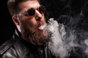Close up portrait of confident bearded man with sunglasses over black background. Serious expression. Playing with smoke.