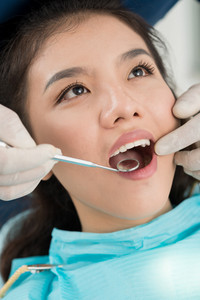 Close-up shot of a patient being examined by a dentist