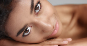 Close up shot of a pretty young wooman with smooth glowing skin relaxing on a white massage table. Studio shoot