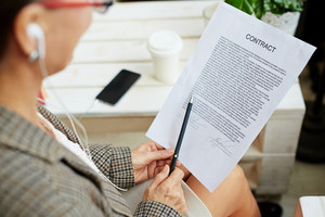 Close-up shot of wrinkled female hands holding black pen and signed business contract, coffee table with paper cup and modern smartphone seen on background