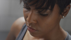 closeup mixed race woman portrait during a rest in fitness workout looking at camera and deep breathing