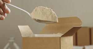 closeup of a spoon takes a flour from box and takes it out