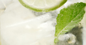 closeup of coctail. Mojito, tonik water with mint and lemon and lime and ice cubes closeup buubles ice texture