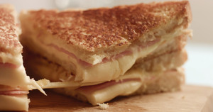 closeup of handmade delicious sandwich with ham and cheese. cutting it and press to show cheese texture. breackfast sandwich