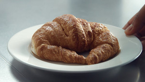 closeup of inox table and man's hand putting a dish with croissant on it in morning light