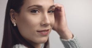 closeup of spanish woman looking at camera on grey background