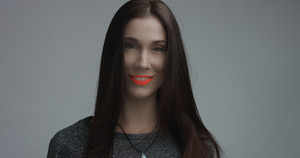 closeup of spanish woman with vivid orange matte lipstick in studio. Straight hair and ideal skin
