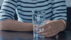 closeup of woman's hand with glass of water touching it