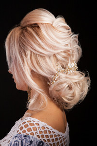 Closeup portrait from behind with beautiful creative hair style in studio. Modern coiffure. Looking good.