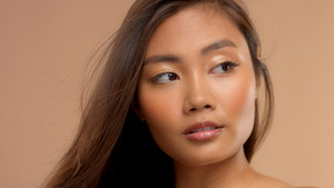 closeup portrait of asian thai japanese model wathing aside with hair blowing
