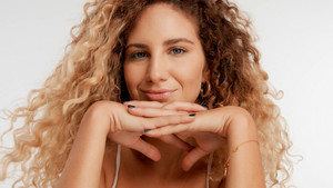 closeup portrait of blonde model with curly hair put her chin on two crossed hands watching to the camera