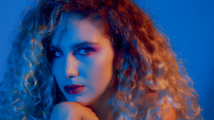 closeup portrait of blonde woman in blue-red light