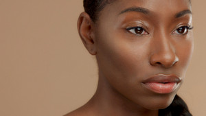 closeup portrait of mixed race black woman watching aside. Ideal skin, natural makeup, shiny glossy eyelids