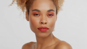 closeup portrait of mixed rase woman with red makeup in studio calm watching to the camera