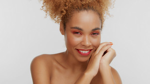 closeup portrait of mixed rase woman with red makeup in studio with hands on face smiling to the camera