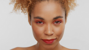 closeup portrait of mixed rase woman with red makeup in studio with head down watching to the camera