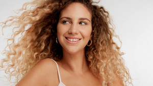 closeup portrait of model with big curly blonde hair blowing and she is smiling and watching aside