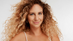 closeup portrait of model with big curly blonde hair blowing and she is smiling slightly