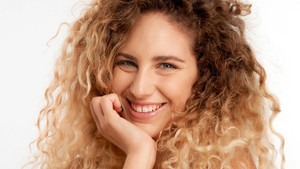 closeup portraitof green eyed model with big curly blonde hair, ideal skin smiling wide