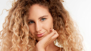 closeup portraitof green eyed model with big curly blonde hair, ideal skin with chin on hand watching to the camera smiling slightly