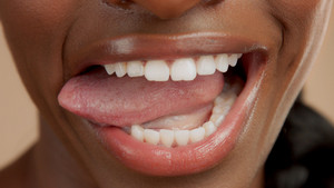 closeup shoot of black womans mouth with tongue out