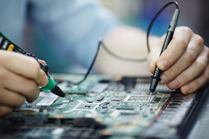 Closeup shot of male hands testing electric current voltage in circuit board of disassembled laptop using multimeter tool on table in maintenance shop