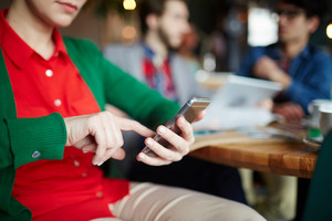 Closeup shot of young woman using smartphone in cafe, holding phone in hands and typing text message looking at screen with people in background