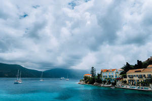 Cloudscape over Fiskardo village buildings with orange brick roofs. Yacht boats looking for shelter in the bay. Kefalonia Island Greece