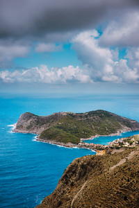 Cloudscape view of Assos village and blue sea bay. Stunning clouds above the penincula. Kefalonia island, Greece