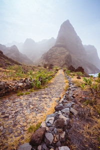 Cobbled hiking path to Ponta do Sol over amazing arid Aranhas valley with huge mountain peak and house ruins. Santo Antao Island, Cape Verde