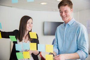Colleagues Smiling While Discussing Over Notes Stuck On Glass