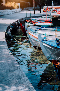 Colorful fishing Boats docked alongside close to quay on the coast of greek island, mediterranean sea scene