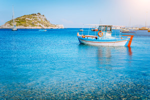 Colorful greek fishing boat at the calm clear water on early summer morning. White rock at the background