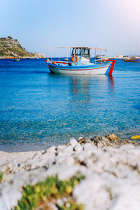 Colorful greek fishing boats at the calm clear water on early summer morning