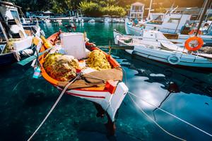 Colorful Greek fishing boats in small port harbor of Kioni on Ithaka island, Greece