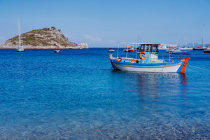 Colorful greek Mediterranean fishing boat at the calm clear blue sea water bay on early summer morning. White rock at the background