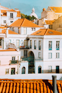 Colorful red and white citycape of Lisbon. Historical downtown built on the side of the hill. Bright sunny summer day