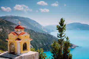 Colorful shrine Proskinitari on pedestal. Amazing sea view to Greece coastline in the background
