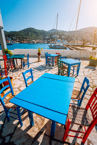 Colorful table and chairs in a typical tavern by the sea. Greek fishing village at hot summer day