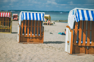 Colorfuled striped roofed chairs on sandy beach in Travemunde. A blurred couple sitting on beach in background. Lubeck, Germany