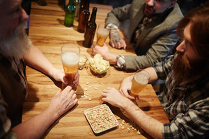 Company of buddies sitting by wooden table and talking by glass of beer