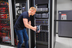 Computer Engineer Installing Server Into Blade Enclosure