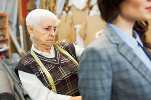 Concentrated dressmaker looking at jacket back