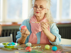 Concentrated senior woman thinking about color of Easter egg