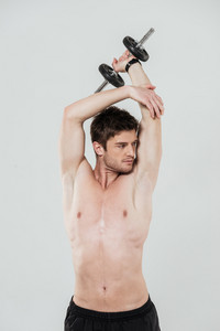 Concentrated shirtless sportsman doing exercises with a dumbbell isolated over white background